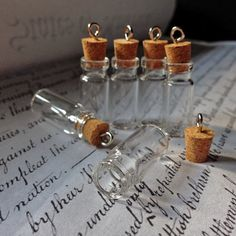 DIY empty glass bottles.  Medium message bottle pendant necklaces with eye loops and corks. Buy in bulk and save. Look for coupon codes on Facebook by beadingmom