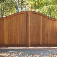 Tongue-and-groove construction for a solid-front wooden driveway gate. This style offers the best privacy. The stain allows the natural wood grain to come through, which softens up the look. Wooden gate designed and installed by Tri State Gate in Bedford Hills, New York.