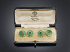 This remarkably rare pair of Faberge jeweled and enameled cufflinks displays the outstanding artistry for which this legendary firm is known. Crafted by Faberge goldsmith master August Frederik Hollming of the St. Petersburg workshop (1898-1908), each 14K yellow gold link boasts a magnificent red cabochon ruby encircled by a field of transparent green guilloche enamel, while chains of rose gold connect the links.