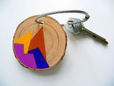 "* * *SOUTHWESTERN STYLE* * *  This handpainted wooden keychain is named ""southwestern style,"" reminiscent of the mountain ranges out west with a tribal color flare. The color scheme features a burnt sienna, purple, golden yellow, and pink. I hand painted this design on a pine wood tree branch slice. It can be used for your keys, as a zipper pull, or as a backpack or purse accessory."