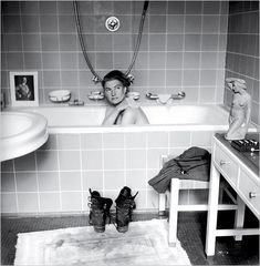 "Lee Miller sneaks a bath in Hitler's apartment after the fall of Berlin, 1945. She later explained blithely, ""I had his address in my pocket for years."" [Photo by David E. Scherman; source NYT] ""She got Scherman to photograph her, unclothed, in Hitler's bath,"" writes Lucy Davies in The Telegraph. ""Her boots are placed in the foreground, covered in the dust of Dachau, which she had visited the day before. The juxtaposition belonged to that Surrealist universe in which dream and coincidence…"