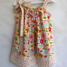 This dress is made from high quality 100% Cotton. The fabric is a pretty combination of red, pink, soft green, aqua and lemon on a cream background.It ties up with an adjustable bow on one side.As your child grows this bow can be loosened to give more room under the arms and it looks equally gorgeous worn as a tunic with a pair of leggings.*measurements (to indicate length) have been taken from under the arms and down the side of the dress to the hemsize 3 - 39.5cmsi...
