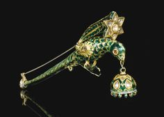 AN ENAMELLED GOLD TURBAN ORNAMENT IN THE FORM OF A PARROT (TURRA), NORTH INDIA, 19TH CENTURY perched on a scrolling leaf issuing from beneath an elongated tail, the body decorated with bright green enamel feather details, including two gem-set eyes, a large flowerhead set with jargoons and leafy stem supported on the back, with a domed pendant suspended from the beak, later mounted as a brooch