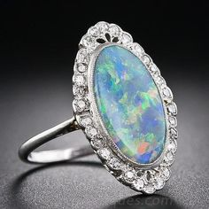 An entrancing elongated oval black opal displaying a full color palette: green, blue, yellow. orange and red, is elegantly presented in an Edwardian-era platinum and diamond mounting - circa 1910. The delicately handcrafted scalloped frame glitters with tiny round diamonds supported by a lovely scrollwork gallery. This dreamy antique jewel measures just over 7/8 inch long by 9/16 inch wide.