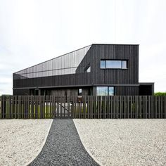 "Residential Architecture: House in Marupe by Open AD: ""..A roof terrace can be glimpsed between the metallic grey timber beams that surround a two-storey house near Riga, Latvia..Doors from the two first-floor bedrooms lead directly onto the screened upper terrace, above an open-plan living area that is visible through a circular roof light."