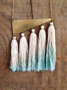 Five raw silk tassels, tied by hand and secured with hammered brass wire, dangle gracefully from a brass pendant. The silk is dip dyed a lovely