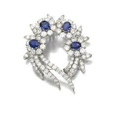 SAPPHIRE AND DIAMOND BROOCH, 1960S, Of foliate design set with four sapphire and diamond oval clusters each centring on an oval sapphire within a surround of brilliant-cut diamonds, interspersed with brilliant-cut diamond set leaves.