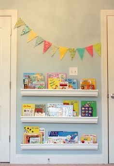rain gutters used to display books-love the flags such a great way to incorporate color into her room.