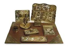 AN ASSEMBLED GILT-BRONZE AND GLASS 'GRAPEVINE' NINE PIECE DESK SET,  BY TIFFANY STUDIOS, FIRST QUARTER 20TH CENTURY, ALL STAMPED 'TIFFANY STUDIOS NEW YORK' AND VARIOUSLY NUMBERED, Price realised  USD 2,500