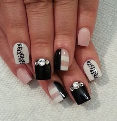 Black and white leopard nail art design with hints of nude nail polish.  The striped designs look perfect with the combination of the colors as well as the embellishments on top.