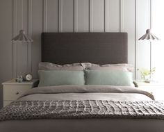 Panelled wall with tall headboard and hanging pendants