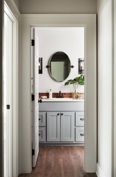 The guest bathroom has really earthy tones to it with the cool grey cabinetry, sleek black hardware, and a warm brown wood detail along the back of the cabinets. The lighting fixtures on either side of the mirror in this bathroom added an interesting detail that sets it apart.