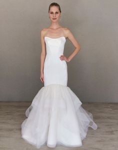 White / Oyster silk faced duchess trumpet bridal gown with a skirt of cascading horsehair edged tulle and dotted tulle. Strapless soft scoop neckline with a jeweled belt at the natural waist. Also available with plain tulle.