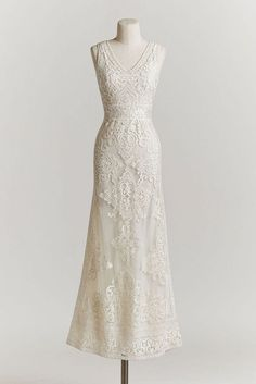 Vintage Wedding Dress: This delicate, ivory tulle gown features a plunging-v neckline and filigreed embroidery throughout the bodice and column skirt.