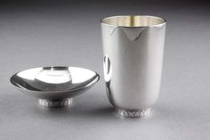 "Two rare Georg Jensen sterling silver items designed by Count Sigvard Bernadotte for Georg Jensen in the 1930's. The first is a cigarette cup, design number 825A, and the second is a candy dish, design number 825 (both items carry the design number on the base). Both have the same simple but elegant design, and rest on the same arch patterned foot. Both items are hallmarked ""Georg Jensen, Denmark Sterling, 925S"", and both have the designers signature ""Sigvard"" along with the pattern number…"