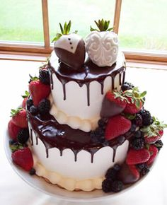 Wedding cake with yummy chocolate strawberries and mix berries cascading down and around.