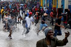 Supporters of the Fanmi Lavalas political party splash around in flood waters in Port-au-Prince. Haiti has planned a re-do election on Sunday, which is still expected to proceed despite the hurricane. Photo by Carlos Garcia Rawlins/Reuters