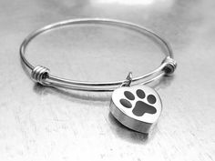 This wire bracelet is also a cremation vessel to hold the ashes of a loved one. This stainless steel bracelet measures up to 10 inches and can sized based on your preference and has a 5/8 inches heart with a paw print and has a screw at the top for easy access to the inside of the urn.  This is a beautiful way to remember your beloved friend.  There are reflections on the pendant in the image that are not part of the bracelet.  Gift boxed.