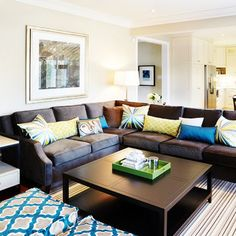Brown sofa with bright pillows.  Sealy Design Inc. To match the new kitchen colors?