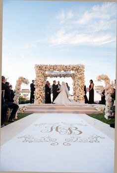 The bride and groom were married in a traditional Jewish ceremony beneath a floral-embellished chuppah. The white aisle runner was emblazoned with the couple's monogram in gold. #weddingceremony #decor Photography: Handeland Tesoro Photography. Read More: http://www.insideweddings.com/weddings/oceanfront-ceremony-ballroom-reception-in-southern-california/575/