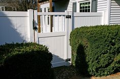 A white vinyl fence lined with evergreens. The Vande Hey Company, Inc.