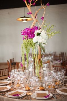 Branches, hanging green amaranthus, white hydrangea and fuchsia orchids.