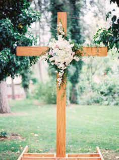 DIY wooden altar decoration with flowers at a garden wedding.