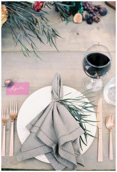 Place setting of white china with a gray hemstitched linen napkin, gold flatware and a place card with calligraphy by Plume Calligraphy & Design. Styling by Lauren Emerson Events & Design. Image by Melanie Gabrielle.