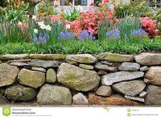 Droge steenmuur, de stijl van New England, en kleurrijke tuin.