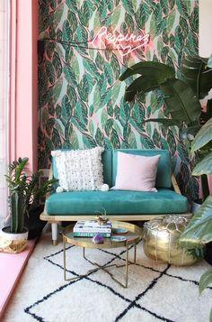 Modernes Wohnzimmer Jungle Stil. Grüne Blatt-Tapete, große Pflanzen, Sitz Pouf in Gold. Inspiration für Kleines Wohnzimmer mit Zwei-Sitzer Sofa und flauschigem Teppich