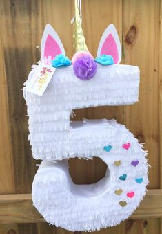 Handcrafted pinata made from recycled cardboard Available as a traditional whack pinata Approx. Size (with horn) is 30 Tall 16 wide 4 Deep Size of Number One is 24 Tall Holds approx. 4-6 pounds of candy, confetti or other goodies (not included) Easy access opening on top to fill