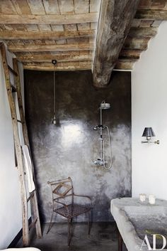 A guest bath has a concrete-and-resin shower with Lefroy Brooks fittings; the stone sink is antique.