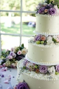 Beautiful threetiered wedding cake decorated with lilac and yellow flowers