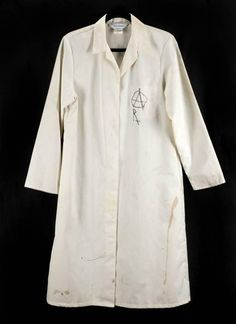 """A white lab coat worn by Kurt Cobain at the September 1, 1991, Abend In Wien concert festival in Rotterdam, seen in the Nirvana video for """"Lithium"""" and in the film 1991 : The Year Punk Broke . The white coat, made by Alexandro of Scotland, has an anarchy symbol drawn in black marker on the left breast pocket with an Rx written below. Across the back is text written by Nirvana bassist Krist Novoselic that reads """"Rabbi Dr. Hillel Bronner All one god!! Dilute! Dilute! Dilute! These are the…"""