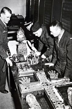 Monument Men-Lt. Col. Ernest Dewald, Director of the MFAA and professor of art and archaeology, Princeton University, and other Monuments Men examine treasures from the Holy Roman Empire after their restitution to Vienna. February 1946.