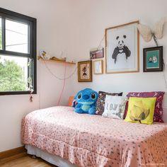 Quarto de adolescente tem parede com quadros e almofadas com estampas variadas.