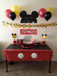 Mickey Cupcake table. Table cloth is made of two dollar store plastic table clothes one red one black and two paper plates for buttons. The wall decorations are scrapbook paper laminated. and a few color balloons from party city.