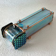 "Easy to hold and breathtaking to view, the oil cell has square glass knobs on either side, affording the viewer an easy turning method. Sitting on Sue's signature tiny brass feet, this is truly a gem of a kaleidoscope. It measures 7"" long x 2-1/2"" wide and stands 2"" tall on Sue's signature little copper-soldered feet."