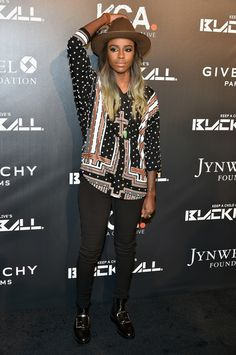 Angel Haze wearing a wide-brim hat, printed blouse, and black jeans