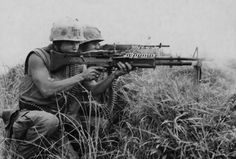 Vietnam War Picture - Machine Gunner and a Rifleman From the Marine Regiment Fire at the Enemy. This is related to my book because these are weapons used and these are what some of the characters would have looked like. Vietnam History, Vietnam War Photos, Vietnam Veterans, Super Hero Shirts, Indochine, History Online, Us Marines, American War, American Story