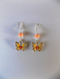 Boucles oreilles papillon émail jaune, orange et strass, perle spirale orange et blanche : Boucles d'oreille par mamiechantal-screations