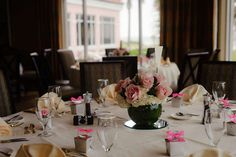 Contrasting Decorations: Accent subtle greenery among classic pastel pink roses and white flower arrangements using dark green short vases for wedding table centerpieces. Wedding guest favors are included in these small silver boxes topped with a bright pink bow to add contrast.