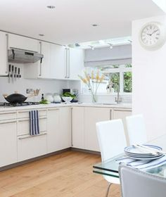 Modern white kitchen with wood floors and blue flowers on glass table