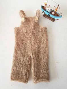 Knitted baby dungaree with 3/4 length legs, Romper in any color of mohair yarn, you like  Suspenders on the bib make an easy fit for any baby. Wooden buttons complete the outfit.  Sizes Newborn through 12 months  The order is for the dungarees only  Made from soft, brushed South African Mohair yarn, sourced locally in Port Elizabeth, from a network of local farmers, chosen for its natural softness and luxury. Hand-wash, roll up in a towel to squeeze out excess water, and dry flat  Shippi...