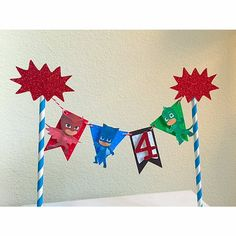 This listing is for an adorable Pj Masks cake topper that is sure to delight your child. It is double layered using heavy card stock. Each pennant is hand embossed. Each character is attached using a 3D foam square. The number of your childs age is machine cut using premium red glittered cardstock and attached using a 3D foam square. The banner is strung together using red and white bakers twine. It is strung using two blue and white striped straws and topped off with 2 glittered pow…
