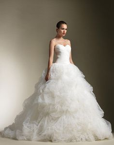 Strapless sweetheart ruched tulle bodice, drop waist with full tulle pick up skirt accented with feathers, buttons down back zipper, chapel length train