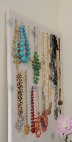 Use your favorite fabric. Cover a cork board. You can use simple pin tacks. A pretty and organized place to hang your jewellry.