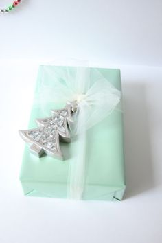 Wrapping idea, Tulle and an ornament! Tulle ribbon is by far the easiest to work with. If you get intimidated by textures then make tulle your go-to ribbon. Simply string an ornament with tulle ribbon and tie a knot!