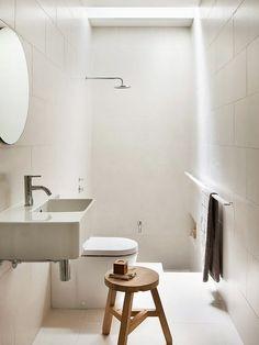 Banheiro branco com banqueta de madeira