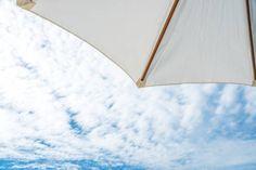 beach umbrella and cloudy blue sky background